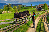 Alpine rural landscape and young woman caressing his beautiful  horse,Bran,Transylvania,Romania,Europe