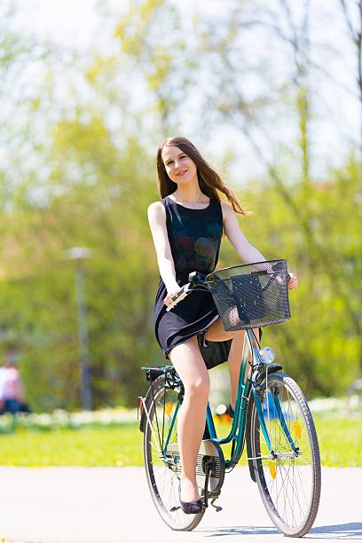 young woman rides a bicycle - mini dress stock photos and pictures
