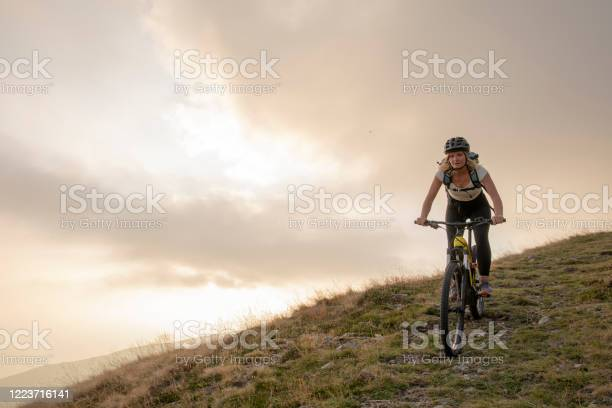 Photo of Young woman rides up grassy hillside on electric mountain bike