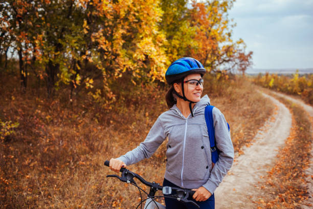 Young woman riding a bicycle in autumn field Young woman riding a bicycle in the field in the morning female biker resting stock pictures, royalty-free photos & images