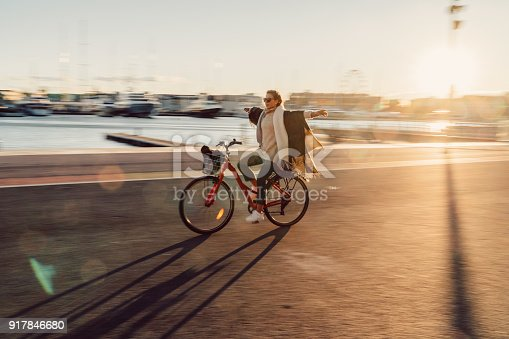 Relaxed woman riding a bicycle on sunset
