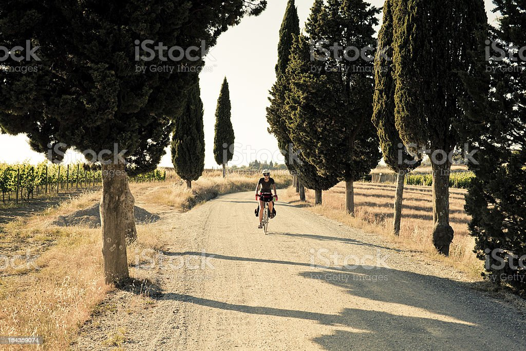 Young Woman Riding a Bike in the Countryside of Tuscany stock photo