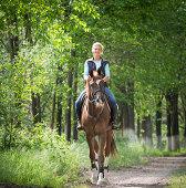 Young woman riding a horse through woodland