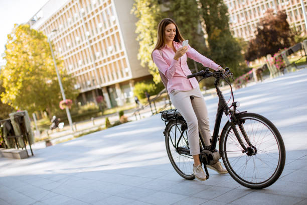 Young woman riding an electric bicycle and using mobile phone in urban environment stock photo