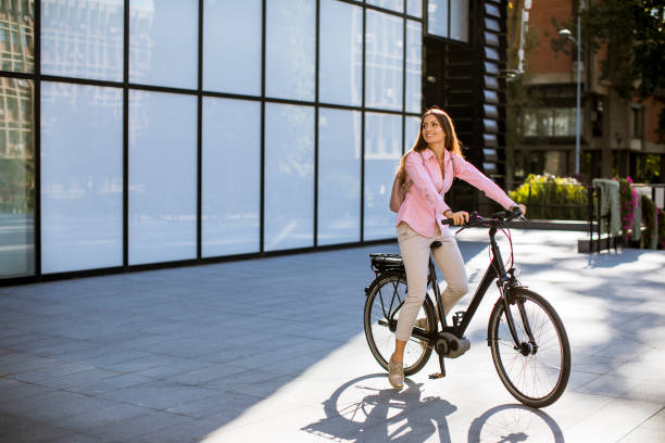Young woman riding an electric bicycle stock photo