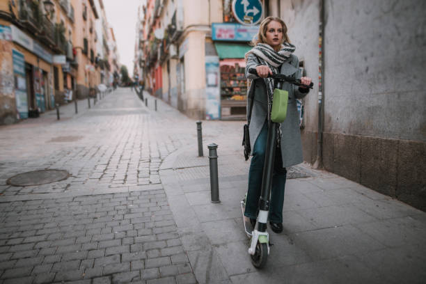 young woman riding an electric scooter in a city - electric push scooter stock photos and pictures