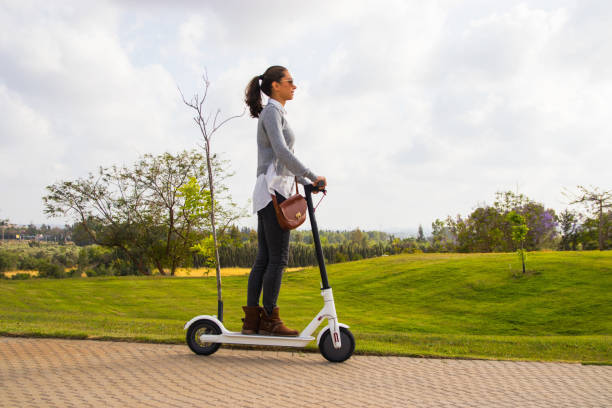 a young woman riding an electric scooter in the park - electric push scooter stock photos and pictures