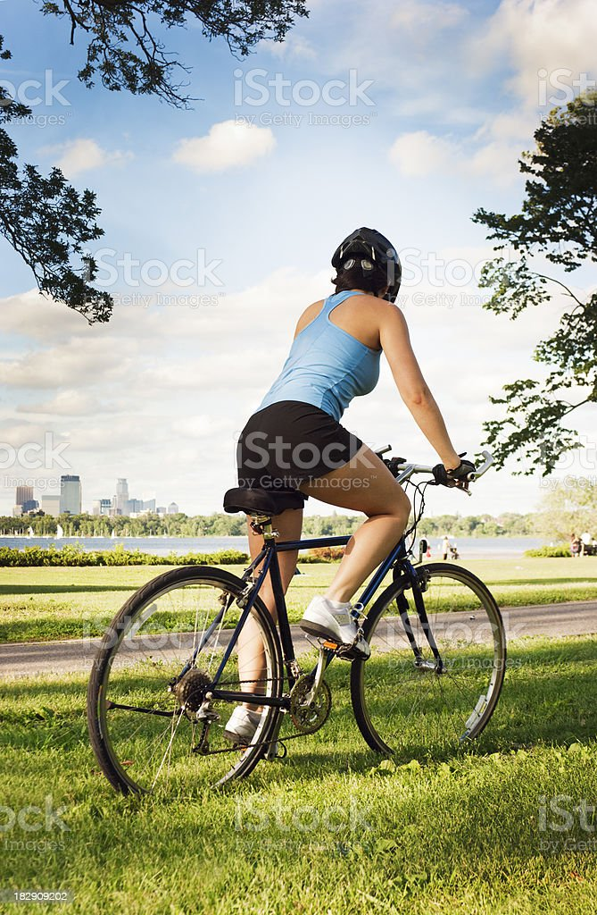 Young Woman Riding Bicycle for Healthy Exercise in City Park royalty-free stock photo