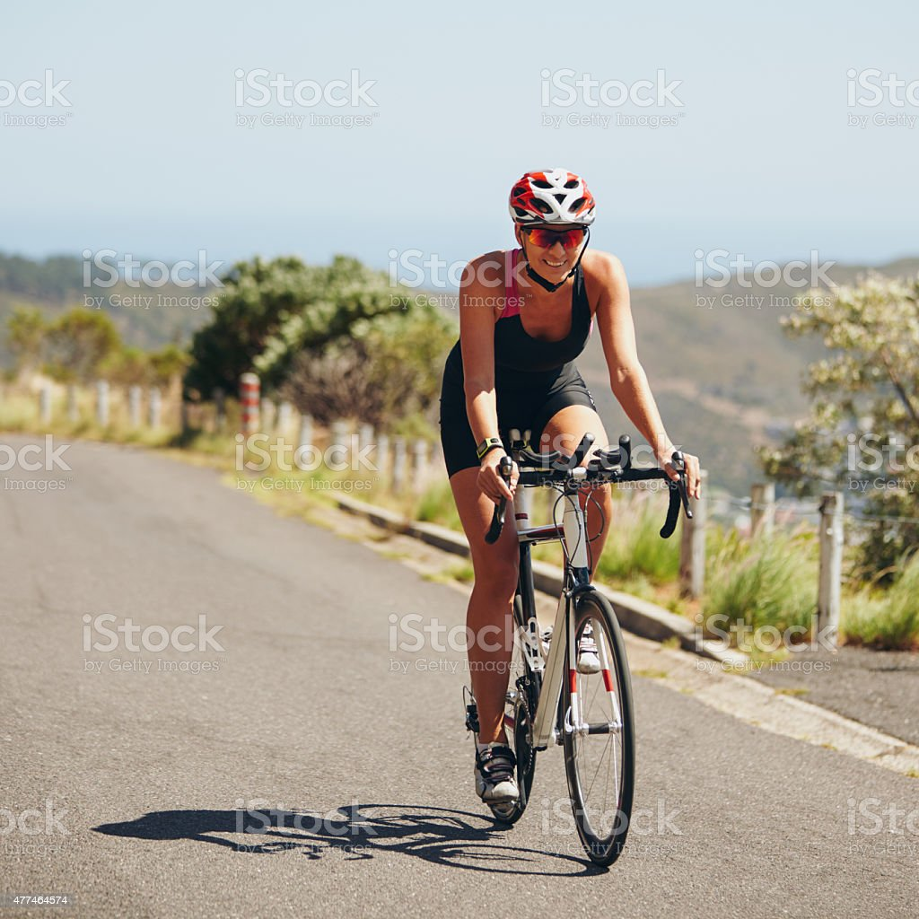 Young woman riding bicycle on open road stock photo