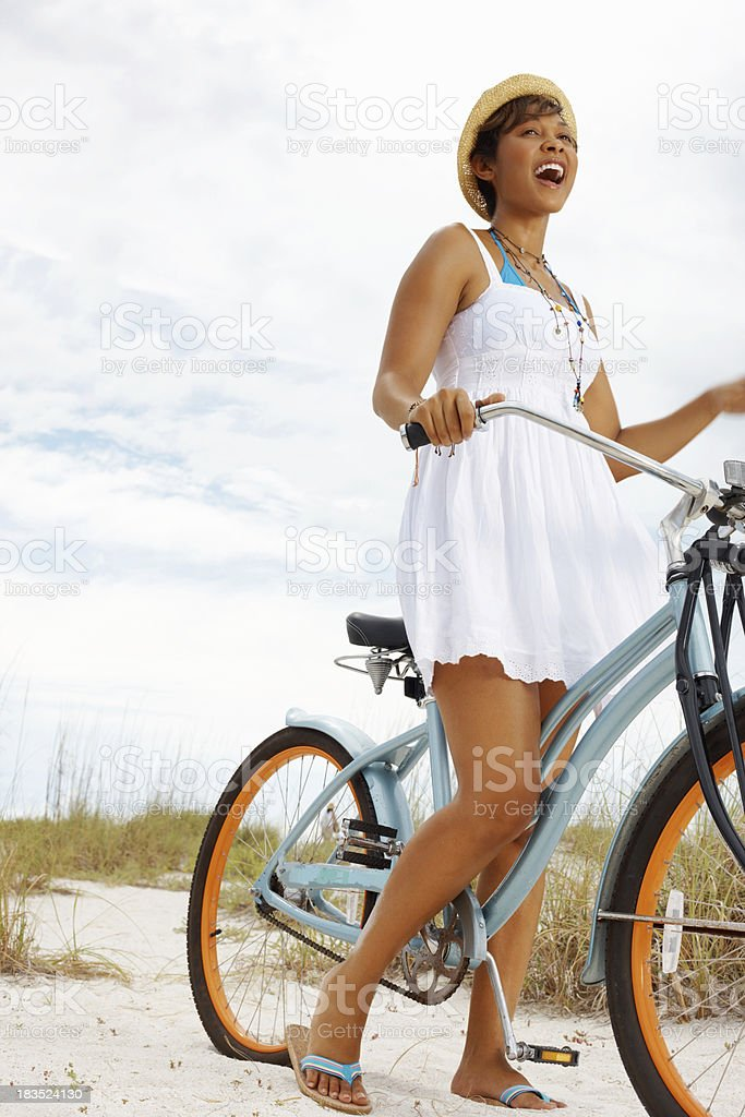 Young woman riding bicycle on the beach against cloudy sky royalty-free stock photo