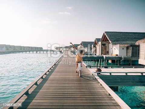 istock Young woman riding bicycle on wooden pier in the Maldives 1298306226