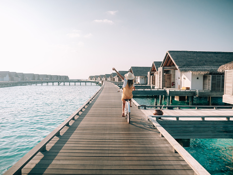 Tropical vacations, young woman with bicycle on wooden pier in the Maldives. Female enjoying bike ride on jetty over coral reef water. Dreamlike destination