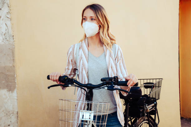 Young woman riding bicycle, wearing medical mask stock photo
