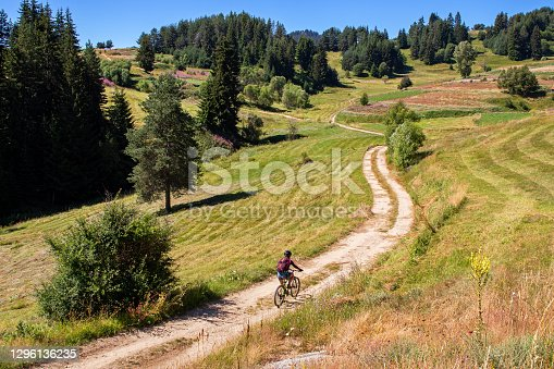 istock Young woman riding bike along dirt road surrounded by grass fields and flowers in a mountain area 1296136235