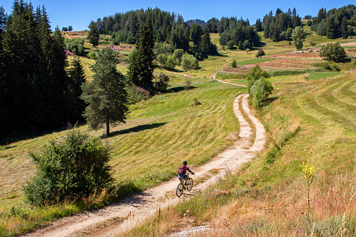 Young woman riding bike along dirt road surrounded by grass fields and flowers in a remote mountain area during summer vacation