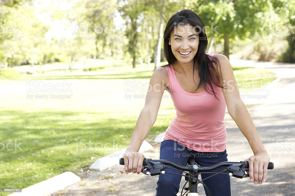 Young Woman Riding Bike In Park royalty-free stock photo