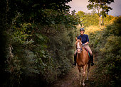 Portrait of a young woman who is riding her tan coloured Arabian horse through the woods on her way to the beach. Photographed the island of Møn in Denmark. Colour, horizontal with some copy space.
