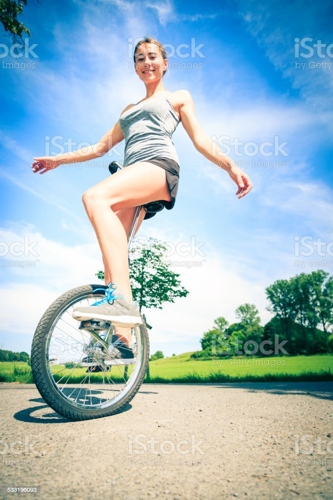 young woman riding her unicycle stock photo