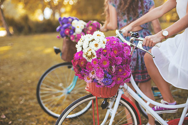 young woman riding her white retro hipster bike - vintage flowers stock photos and pictures
