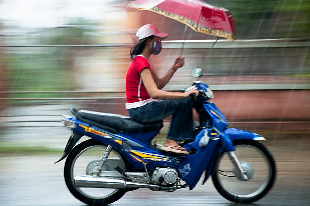 young woman riding in the rain - motorbike, umbrella stock pictures, royalty-free photos & images