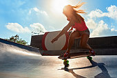 Young woman riding on surf skate