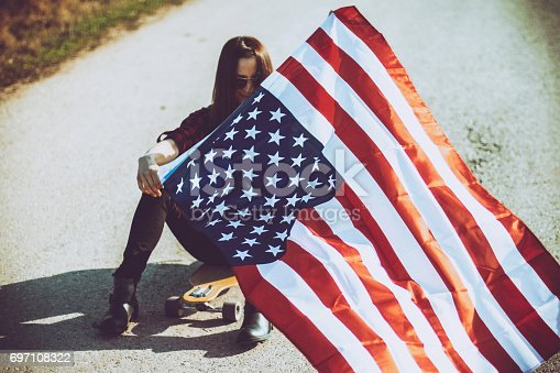 Young woman riding skateboard and waving american flag