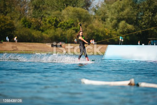 Young woman pulled by towing rope wakeboarding by the sports ramp on the lake
