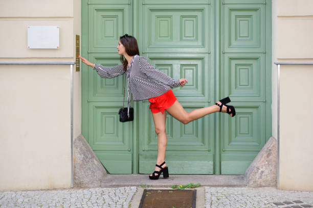 young woman ringing doorbell - squillare foto e immagini stock