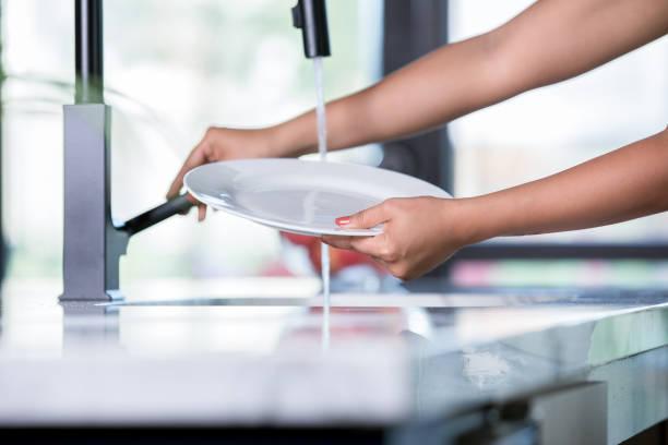 junge frau spült platte während am spülbecken stehen und abwasch - wasch oder spülbecken stock-fotos und bilder