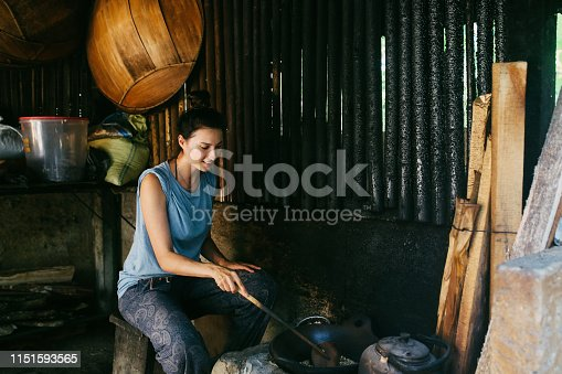 Young woman sitting and roasting the famous Balinese - Indonesian coffee - kopi luwak. Raw, roasted beans.