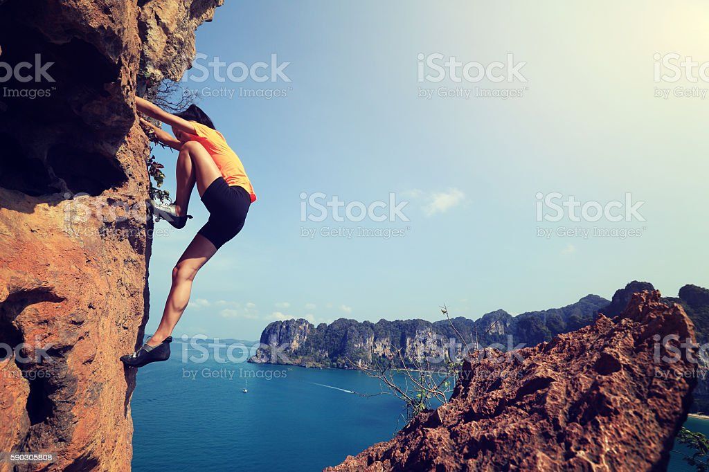 young woman rock climber climbing at seaside mountain rock stock photo
