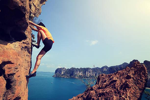 young woman rock climber climbing at seaside mountain rock - rock climbing stock photos and pictures