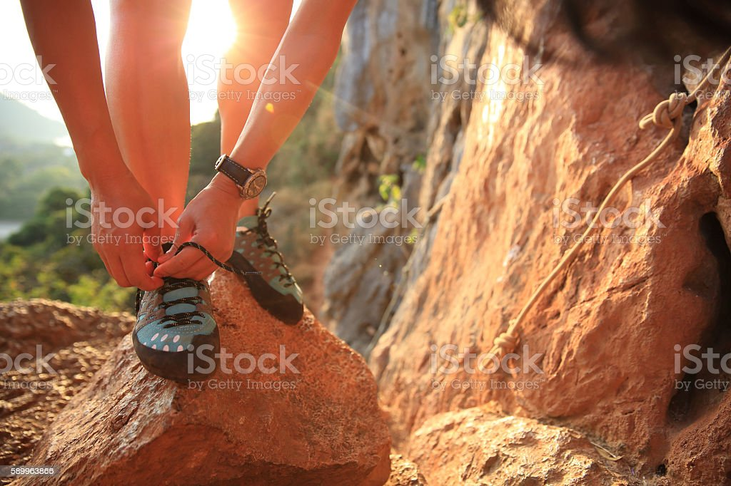 young woman rock climber tying shoelace at mountain rock stock photo