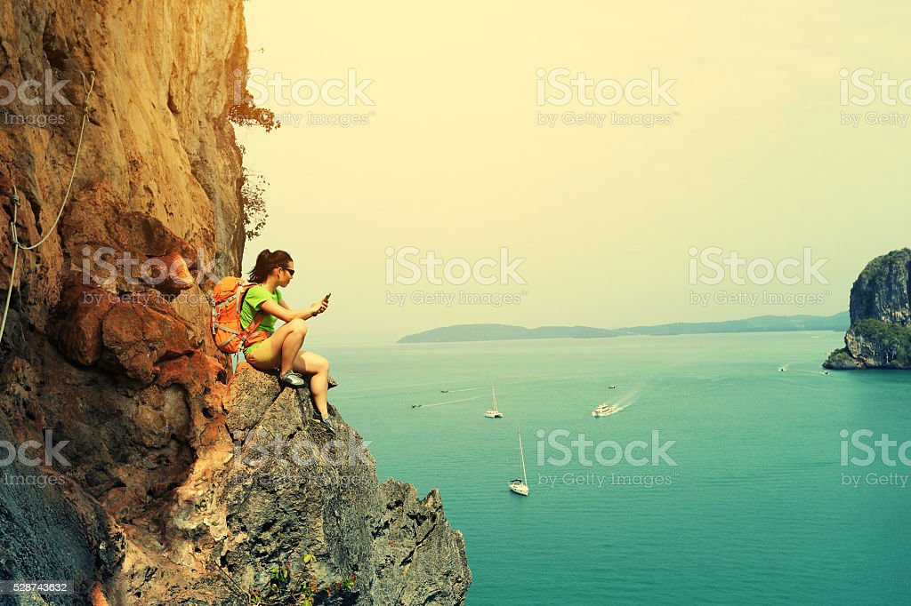 young woman rock climber use smartphone at seaside mountain cliff stock photo