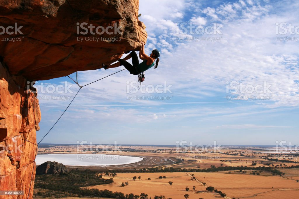 Young woman rock climbing in the desert stock photo