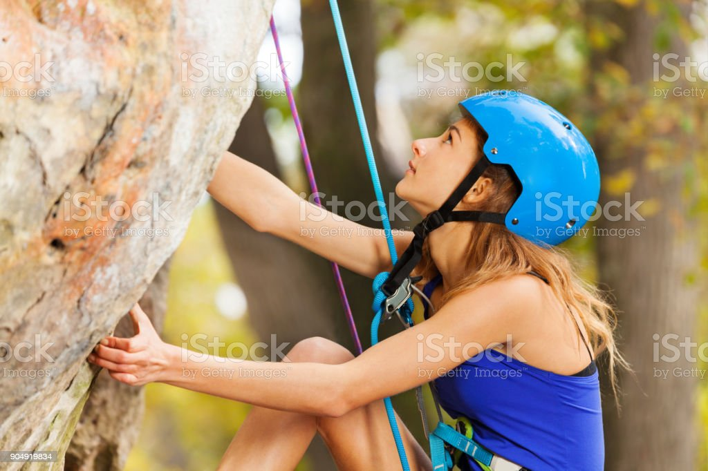 Young woman rock climbing to top of the mountain stock photo