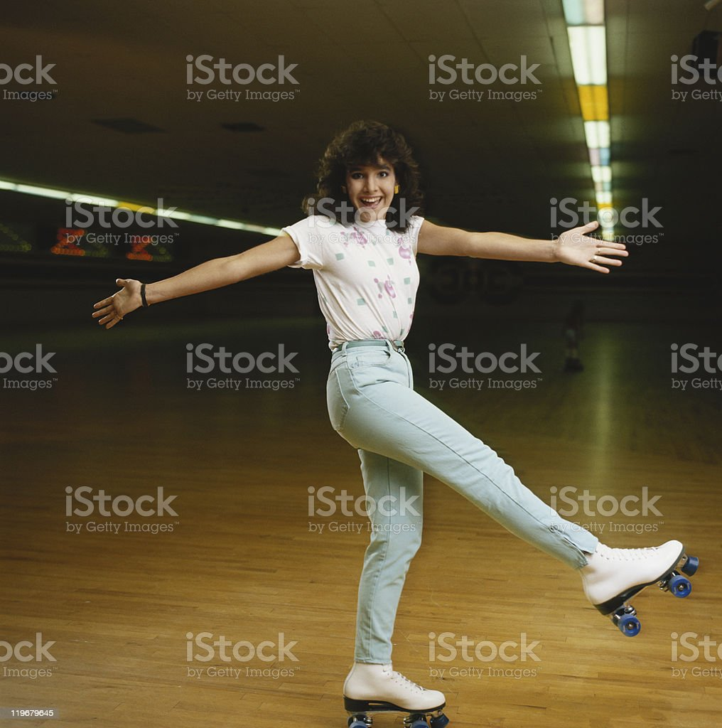 Young woman roller skating on wooden floor, smiling, portrait stock photo