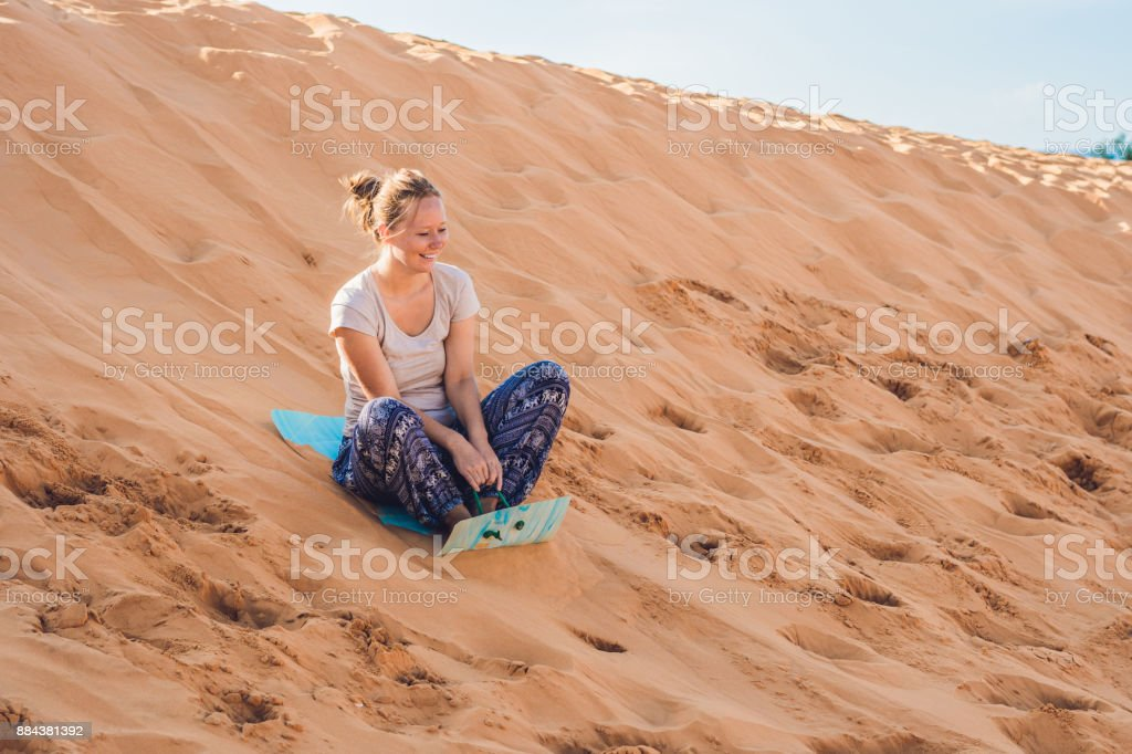 Young woman rolls on a toboggan in the sledge in the desert stock photo
