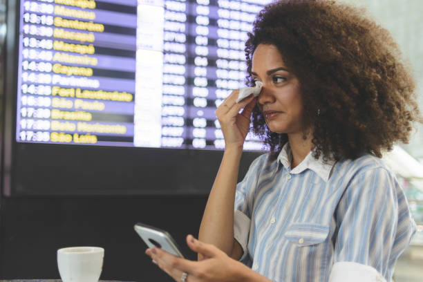 Young woman rubbing her eyes with a tissue paper in the airport stock photo