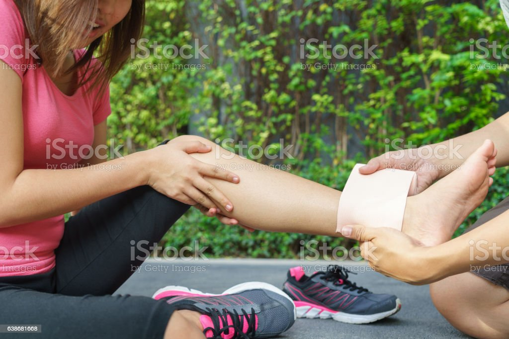 Young woman runner ankle being applied bandage by man stock photo