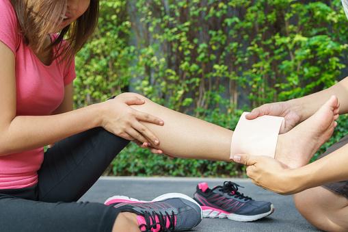 Young Woman Runner Ankle Being Applied Bandage By Man Stockfoto und mehr Bilder von Asiatischer und Indischer Abstammung