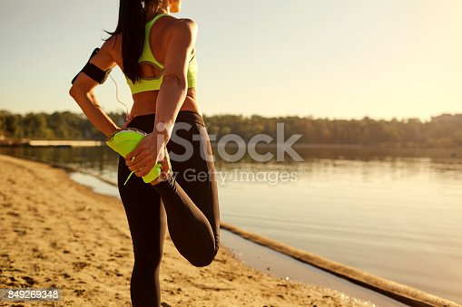 istock Young woman runner doing warm-up stretching her legs in a park. 849269348
