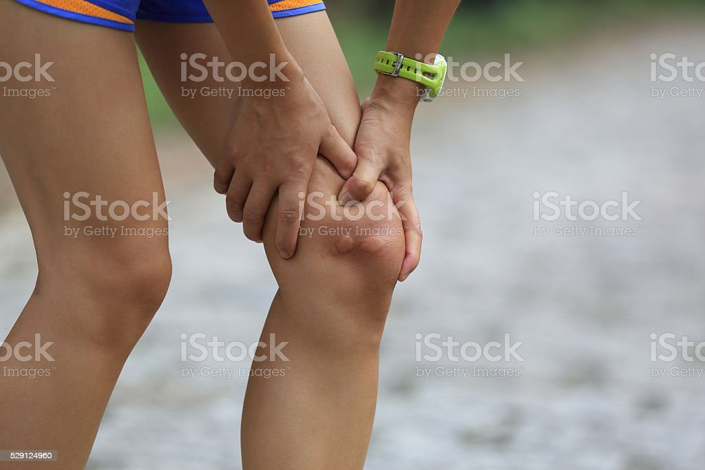 young woman runner hold her injured knee stock photo