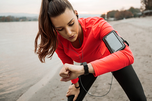 Young woman runner in sportswear uses a smart tracker on the beach