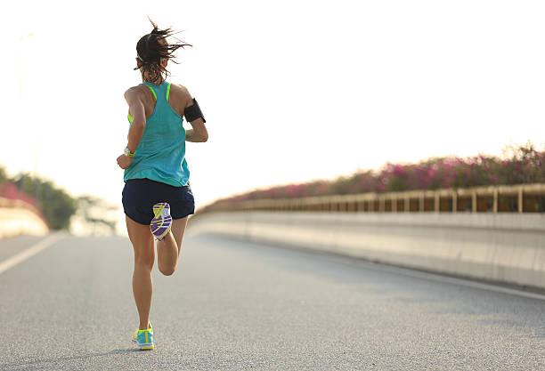 junge frau läufer laufen auf city bridge road - joggerin stock-fotos und bilder