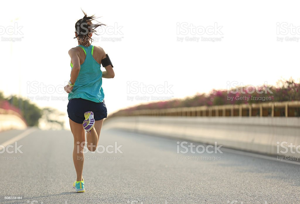 young woman runner running on city bridge road stock photo