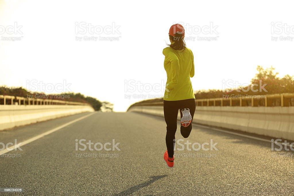 Jovem mulher de corredor correndo na cidade bridge road foto royalty-free