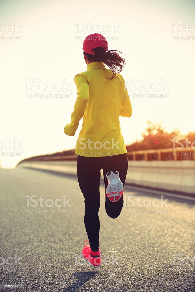 Corredor de mulher jovem correndo na rua da cidade foto royalty-free