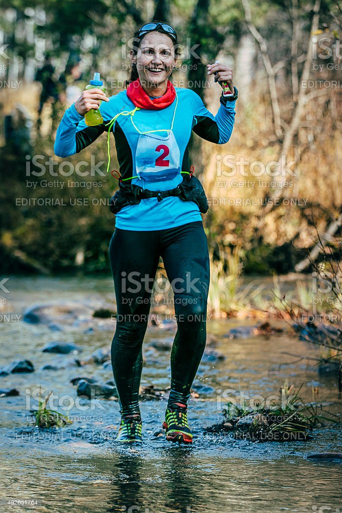 young woman runner smiling while crossing a mountain river stock photo