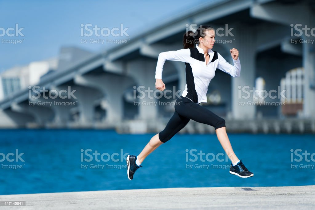 Young Woman Runner Sprinting by Bridge royalty-free stock photo